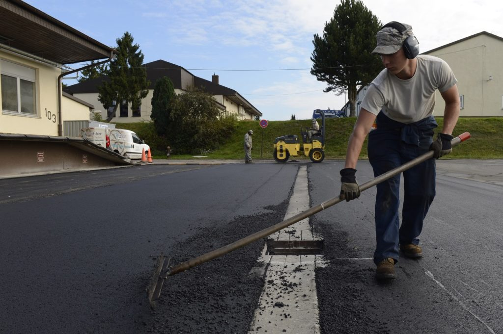 man fixing asphalt