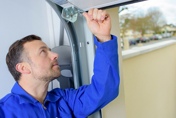 man installing overhead garage door